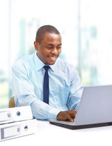 African man on laptop trading stocks
